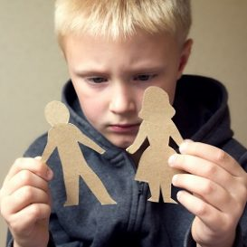 confused child with paper parents will have a custody arrangement settled by a Fort Wayne child custody attorney